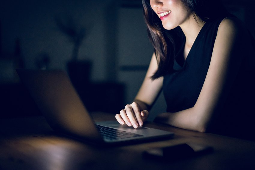 Image of woman smiling and sitting in a dark room on her laptop