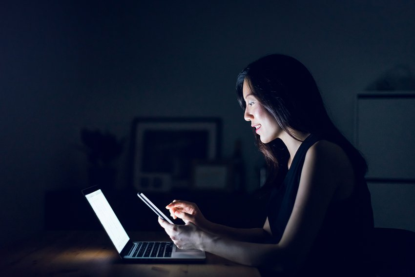 Side view of Asian woman working remote from both a smart device and laptop