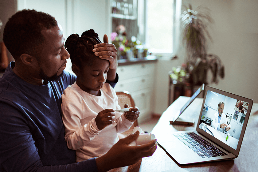 A father consulting with a doctor over video with daughter