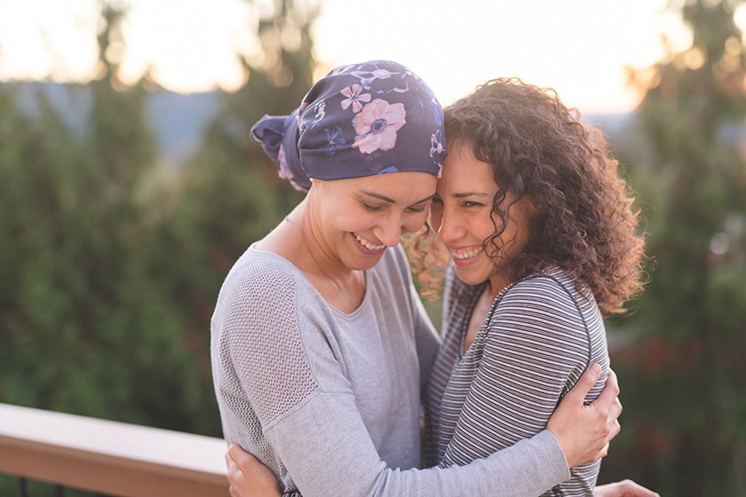 Woman cancer patient hugging her friend